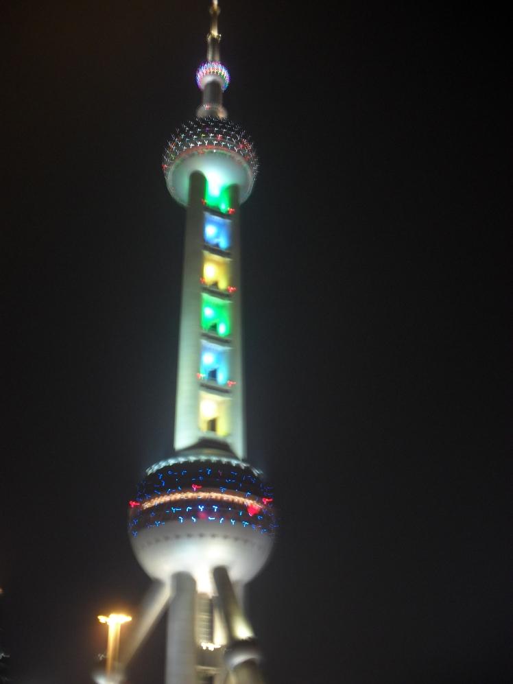 glowing Oriental Pearl Tower at night.